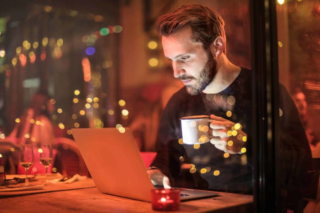 man looking at computer drinking coffee