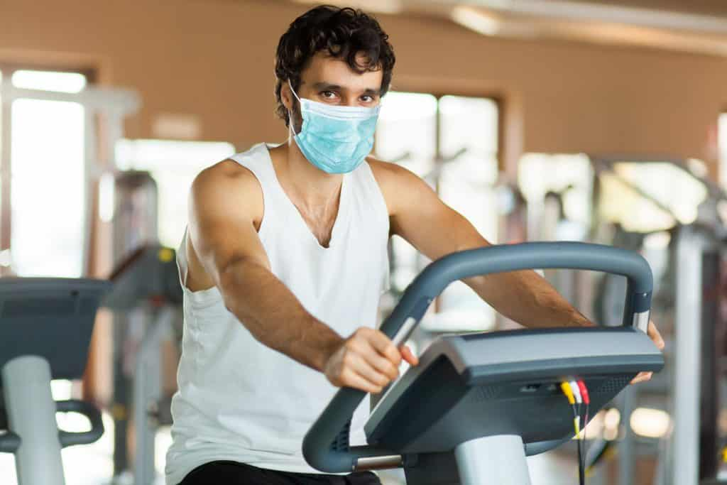 Man in the gym, exercising his legs doing cardio training on bicycle wearing a mask - coronavirus concept