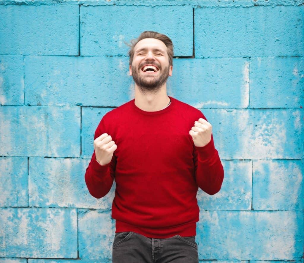 Man happy against blue brick wall