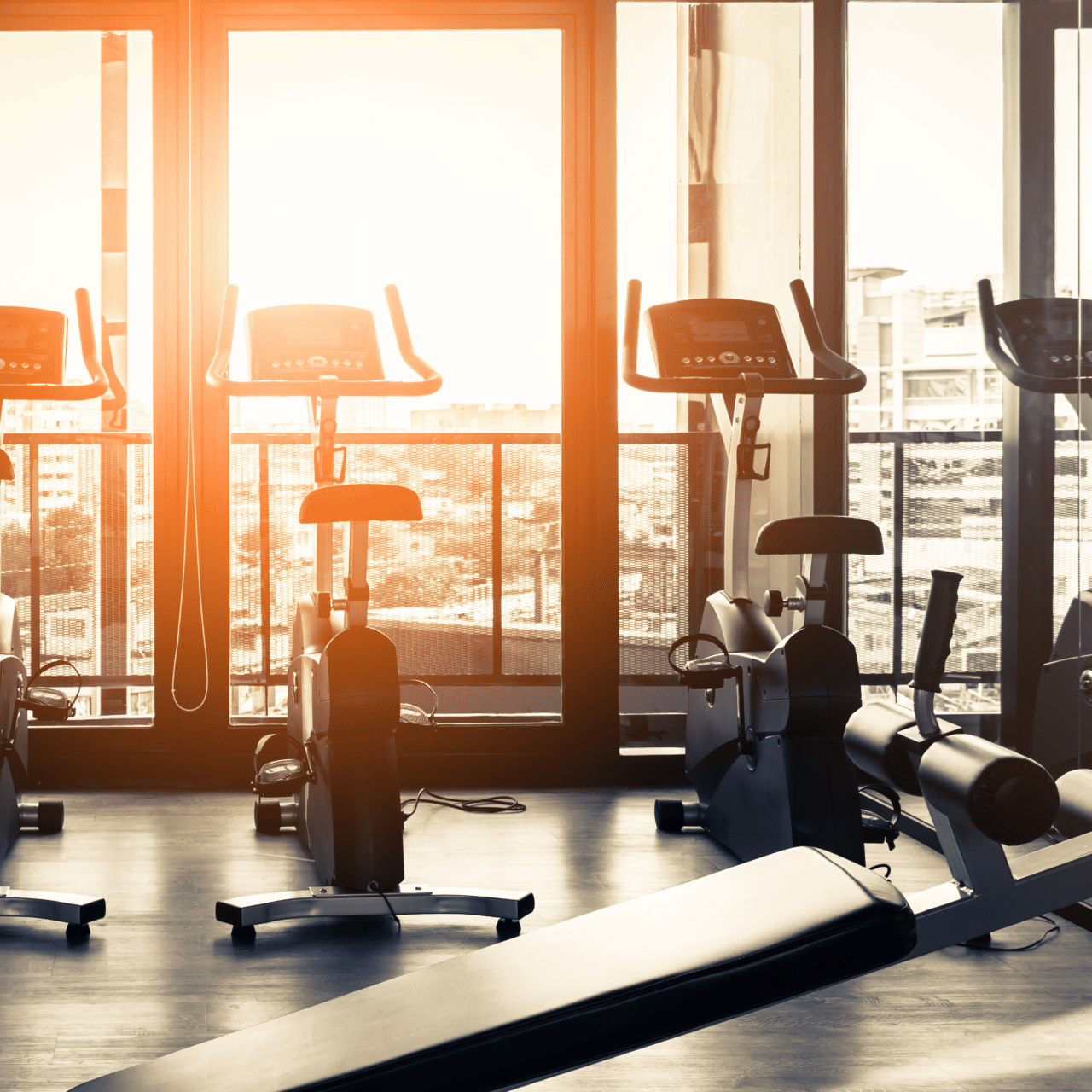 Elliptical in Modern gym interior with equipment. Row of training exercise bikes wheel detail, backlight